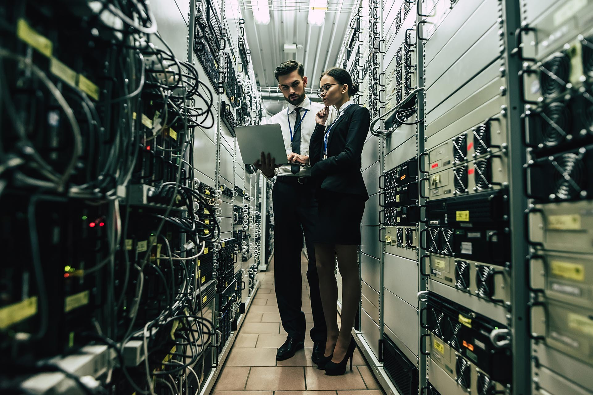 Man and woman IT staff working in data center with laptop doing vulnerability scanning